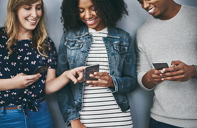 Buy stock photo Studio shot of three young people using their cellphones against a grey background