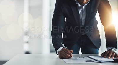 Buy stock photo Cropped shot of an unrecognizable young businessman taking notes while working in his modern office