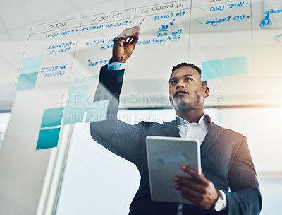 Buy stock photo Shot of a young businessman using a digital tablet while writing notes on a glass wall in an office