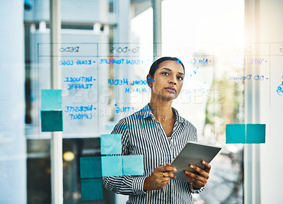 Buy stock photo Shot of a young businesswoman using a digital tablet while brainstorming on a glass wall in an office
