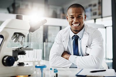 Buy stock photo Cropped portrait of a handsome young male scientist sitting with his arms folded in his research lab