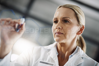 Buy stock photo Cropped shot of an attractive mature female scientist writing down formulas on a glass wipe board while doing research in her lab