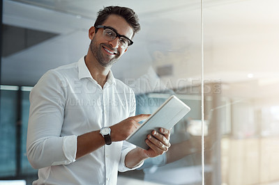 Buy stock photo Cropped portrait of a handsome young businessman working on his digital tablet while standing in the office