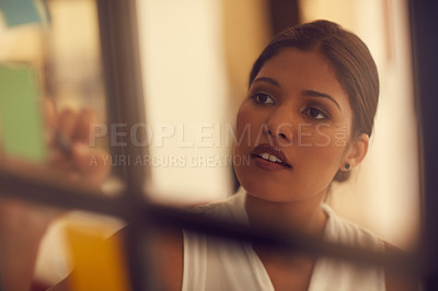 Buy stock photo Cropped shot of a young attractive businesswoman brainstorming on a glass wall in the office