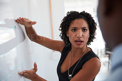 Buy stock photo Cropped shot of a young businesswoman explaining information on a whiteboard to her male colleague in the office