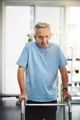 Buy stock photo Shot of a senior man using a walker in a rehabilitation centre