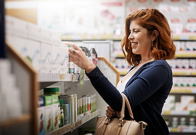 Buy stock photo Shot of a young woman browsing through products in a pharmacy