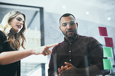 Buy stock photo Shot of a young businessman and businesswoman brainstorming in a modern office