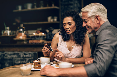 Buy stock photo Shot of a mature couple using a mobile phone together on a coffee date