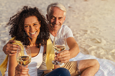 Buy stock photo Portrait of a mature couple having drinks on a romantic date at the beach