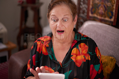Buy stock photo Shot of a senior woman using a mobile phone and looking surprised