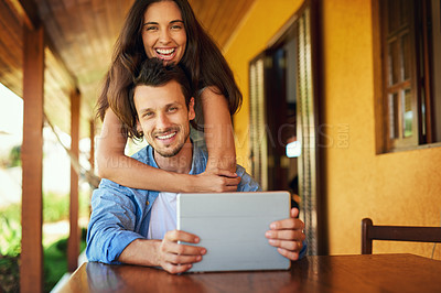 Buy stock photo Portrait of a young couple using a digital tablet together outdoors