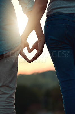 Buy stock photo Rearview shot of an unrecognizable young couple making a heart shape with their hands while standing outside