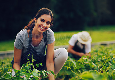 Buy stock photo Portrait of a young woman working in a garden with her husband in the background