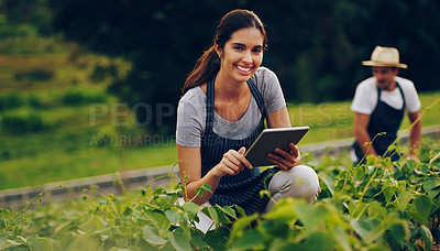 Buy stock photo Portrait of a young woman using a digital tablet while working in a garden with her husband in the background