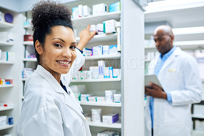 Buy stock photo Shot of a female pharmacist working with her colleague standing in the background