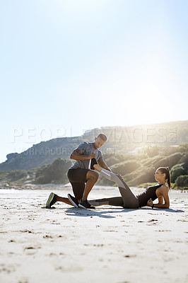 Buy stock photo Shot of a sporty young couple stretching while exercising along the beach
