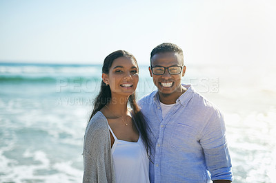 Buy stock photo Shot of a young couple relaxing together at the beach