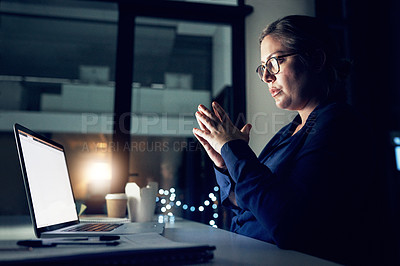 Buy stock photo Shot of a young businesswoman working on a laptop in an office at night