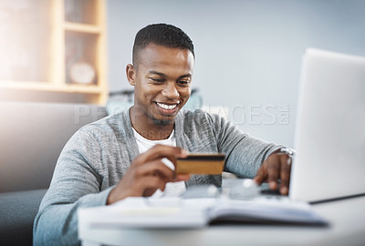 Buy stock photo Shot of a young man using his laptop to shop online at home