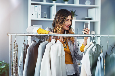 Buy stock photo Shot of a young woman using a mobile phone in her design studio
