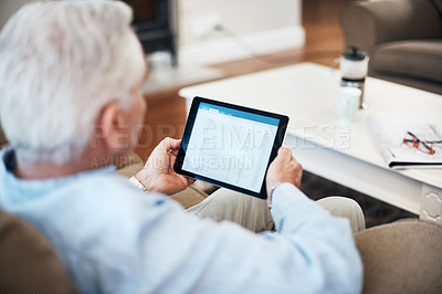 Buy stock photo High angle shot of an unrecognizable senior man banking on his tablet while sitting on the sofa at home