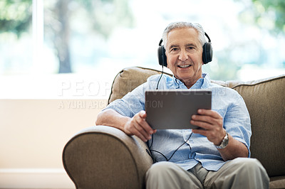 Buy stock photo Cropped portrait of a senior man using his tablet while sitting on the sofa at home