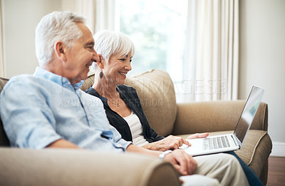 Buy stock photo Cropped shot of an affectionate senior couple using their laptop while sitting on the sofa at home