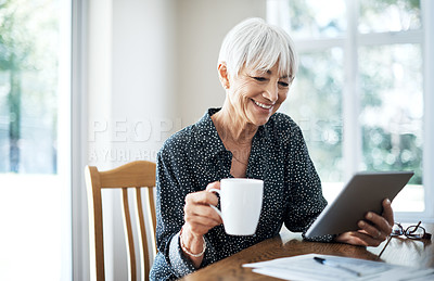 Buy stock photo Cropped shot of a senior woman going through her finances while sitting at the dining room table
