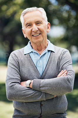Buy stock photo Cropped portrait of a senior man standing with his arms crossed outside on a summer's day
