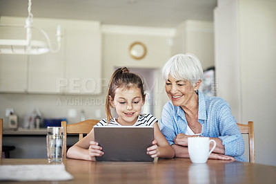 Buy stock photo Shot of an adorable little girl using a digital tablet with her grandmother at home
