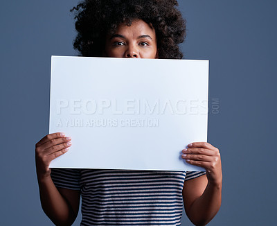 Buy stock photo Studio shot of an attractive young woman holding a blank placard against a blue background