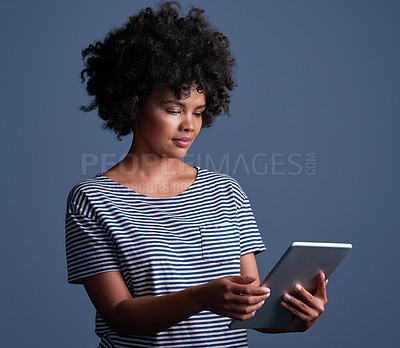 Buy stock photo Studio shot of an attractive young woman using a digital tablet against a blue background