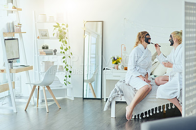 Buy stock photo Full length shot of an attractive young woman applying a face mask to her friend's face during a girls' weekend at home