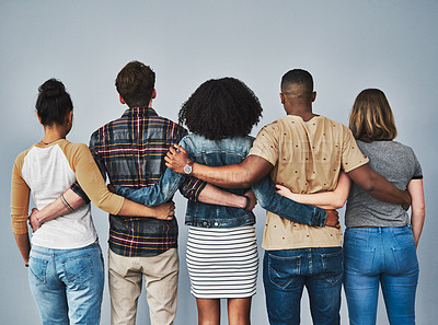 Buy stock photo Rearview studio shot of a diverse group of young people embracing each other against a gray background