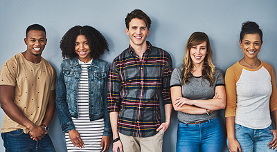 Buy stock photo Studio portrait of a diverse group of young people standing together against a gray background