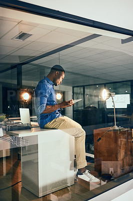 Buy stock photo Shot of a young handsome businessman using a tablet while working late in the office