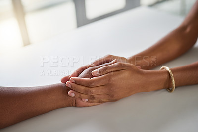 Buy stock photo High angle shot of two unrecognizable businesswomen holding hands in comfort while sitting in their office