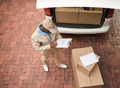 Buy stock photo High angle shot of a young man making a deliveries with a delivery van