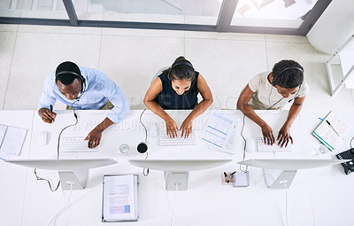 Buy stock photo High angle shot of  a team of young call centre agents working in a modern office