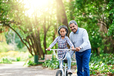 Buy stock photo Cropped portrait of an adorable little girl learning how to ride a bike while enjoying the day outdoors with her granddad