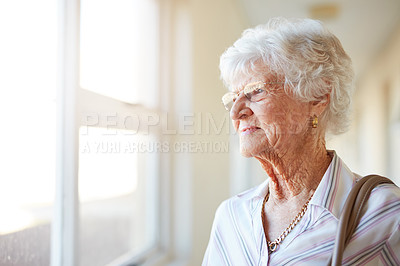 Buy stock photo Shot of an elderly woman looking out of the window before she leaves home