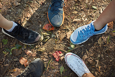 Buy stock photo Low angle shot of a group of friends putting their feet together