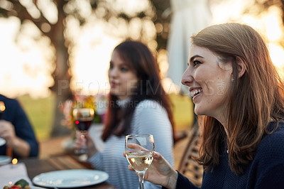 Buy stock photo Shot of a young woman enjoying a meal with her friends outdoors