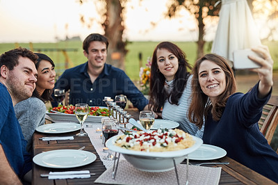 Buy stock photo Shot of a group of friends taking a selfie while enjoying a meal together outdoors