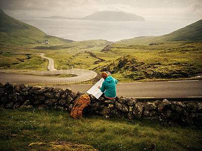Buy stock photo Rearview shot of a unrecognizable woman seated on a small stone wall while reading a map to her next hiking destination outside in nature