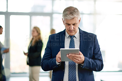 Buy stock photo Shot of a mature businessman using a digital tablet at a convention center