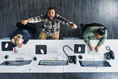 Buy stock photo High angle shot of a call centre agent cheering while working alongside his colleagues in an office