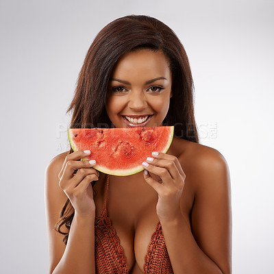 Buy stock photo Studio portrait of a beautiful young woman in a bikini holding a watermelon against a gray background