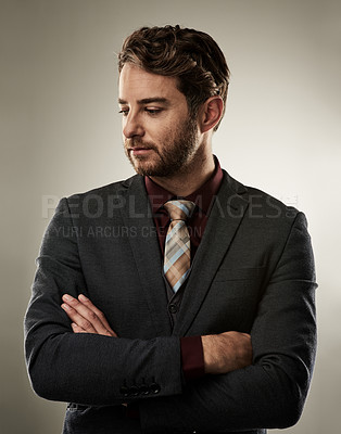 Buy stock photo Studio shot of a handsome young businessman standing with his arms crossed against a grey background